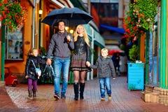 Famille heureuse marchant sous la pluie sur la rue colorée Photographie stock