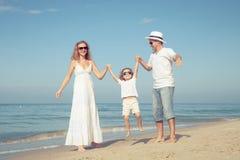Famille heureuse marchant sur la plage au temps de jour Images stock
