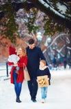 Famille heureuse marchant sur la rue d'hiver aux vacances Image libre de droits