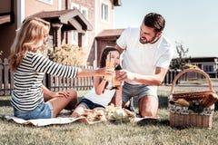 Famille heureuse mignonne passant le temps ayant ensemble un pique-nique Image libre de droits
