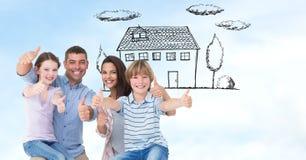 Famille heureuse montrant des pouces vers le haut de signe avec la maison à l'arrière-plan Image stock