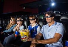 Famille heureuse observant le film 3D dans le théâtre Photos stock