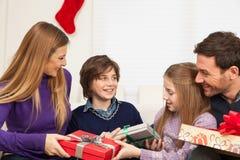 Famille heureuse ouvrant le cadeau de Noël photographie stock