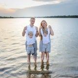 Famille heureuse - père, mère, deux fils sur la plage avec leurs pieds dans l'eau au coucher du soleil Photos libres de droits