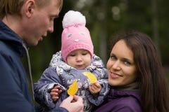 Famille heureuse : Père, mère et enfant - en parc d'automne : papa, pose de bébé de maman extérieure, fille se tenant dans les ma Photos stock