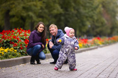 Famille heureuse : Père, mère et enfant - petite fille en parc d'automne : jouer dans l'allée avec des fleurs Image libre de droits