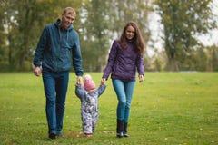 Famille heureuse : Père, mère et enfant - petite fille en parc d'automne : marchant au pré, grand-angulaire Photos libres de droits
