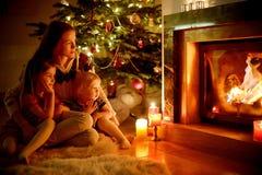 Famille heureuse par une cheminée sur Noël Images libres de droits