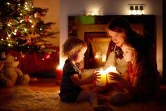 Famille heureuse par une cheminée sur Noël Photographie stock libre de droits