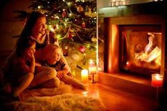 Famille heureuse par une cheminée sur Noël Image libre de droits