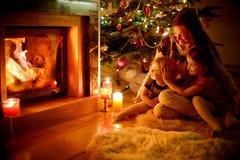 Famille heureuse par une cheminée sur Noël Photographie stock