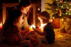 Famille heureuse par une cheminée sur Noël Photos stock