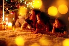 Famille heureuse par une cheminée sur Noël Images stock