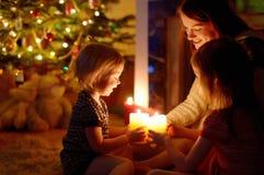 Famille heureuse par une cheminée sur Noël Image stock