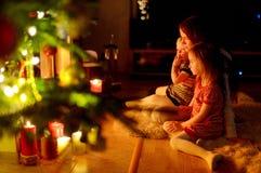 Famille heureuse par une cheminée sur Noël Photos libres de droits