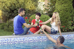 Famille heureuse passant le grand temps ensemble à la piscine Image libre de droits