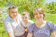 Famille heureuse passant le temps dehors un jour ensoleillé d'été la maman et le papa heureux embrassent le fils en parc le jour  Image libre de droits