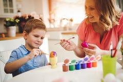 Famille heureuse peignant des oeufs de pâques photographie stock