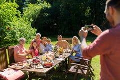 Famille heureuse photographiant par le smartphone en été Images libres de droits