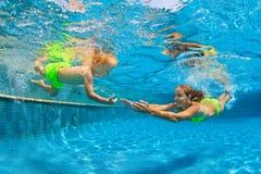 Famille heureuse plongeant sous l'eau avec l'amusement dans la piscine images libres de droits