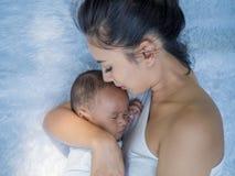 Famille heureuse, portrait de la belle jeune mère asiatique embrassant son bébé nouveau-né avec amour Soins de santé et amour méd photographie stock libre de droits