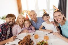 Famille heureuse posant se reposer à une table de fête à la fête d'anniversaire du ` s de fille Photos stock