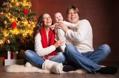 Famille heureuse près d'arbre de Noël à la maison Photographie stock