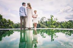 Famille heureuse près de piscine dans Ubud, Bali Photos stock