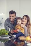 Famille heureuse préparant des légumes ensemble à la maison dans la cuisine photographie stock libre de droits