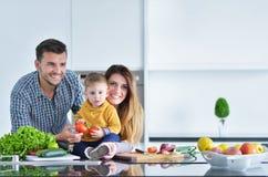 Famille heureuse préparant des légumes ensemble à la maison dans la cuisine photo stock
