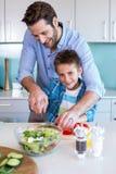 Famille heureuse préparant des légumes ensemble Photos stock