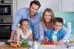 Famille heureuse préparant des légumes ensemble Photographie stock libre de droits