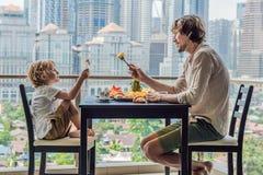 Famille heureuse prenant le petit déjeuner sur le balcon Table de petit déjeuner avec le fruit et le pain de café croisant sur un images libres de droits