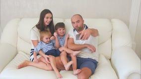 Famille heureuse prenant les selfies drôles au téléphone se reposant sur le sofa banque de vidéos