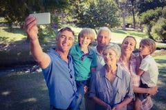 Famille heureuse prenant un selfie en parc Photos libres de droits