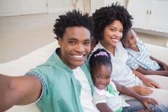 Famille heureuse prenant un selfie sur le divan Image libre de droits