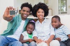 Famille heureuse prenant un selfie sur le divan Image stock