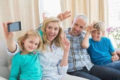 Famille heureuse prenant un selfie sur le divan Photos stock