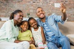 Famille heureuse prenant un selfie sur le divan Images libres de droits