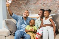 Famille heureuse prenant un selfie sur le divan Images stock