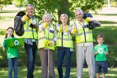 Famille heureuse rassemblant des déchets avec des pouces  Photos libres de droits