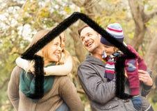 Famille heureuse recouverte avec la forme de maison en parc photos stock