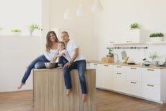 Famille heureuse regardant l'appareil-photo dans la cuisine Photo libre de droits