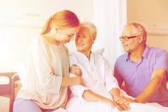 Famille heureuse rendant visite à la femme supérieure à l'hôpital Image stock