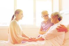 Famille heureuse rendant visite à la femme supérieure à l'hôpital Photos libres de droits