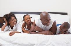 Famille heureuse riant ensemble dans le lit images stock