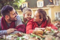 Famille heureuse s'étendant sur des feuilles de chute Image libre de droits