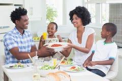 Famille heureuse s'asseyant au dîner ensemble Image stock