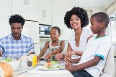 Famille heureuse s'asseyant au dîner ensemble Photographie stock