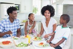 Famille heureuse s'asseyant au dîner ensemble Photo stock